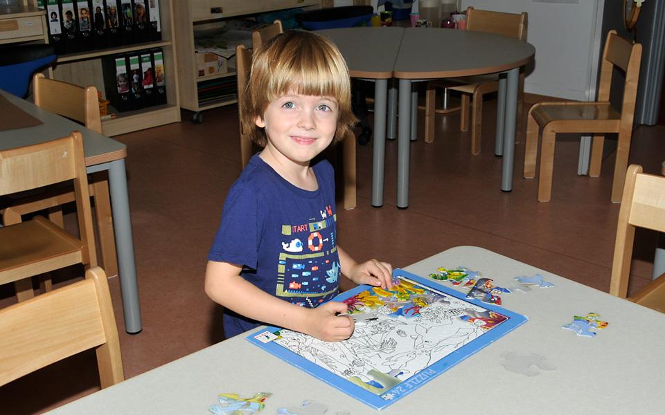 Ein kleiner Junge puzzelt an einem Tisch in der Kita Wiesenpark und schaut dabei in die Kamera
