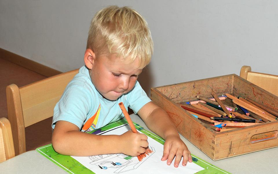 Ein kleiner Junge sitzt am Tisch und malt ein Bild