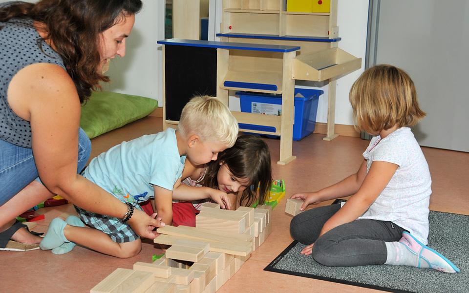 Drei Kinder und eine Erzieherin sitzen auf dem Fußboden und bauen einen Autotunnel aus Holzbausteinen.