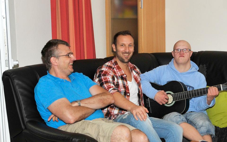 Drei Bewohner des Wohnheims Kamper Weg sitzen auf einem Sofa. Einer der Bewohner spielt Gitarre.