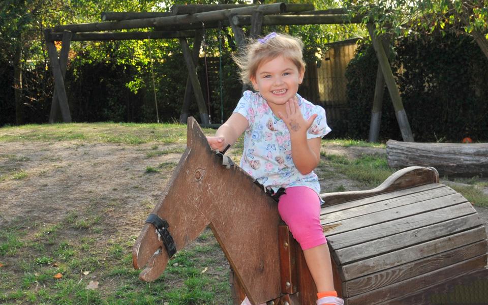 Ein kleines Mädchen sitzt auf einem Holzpferd.