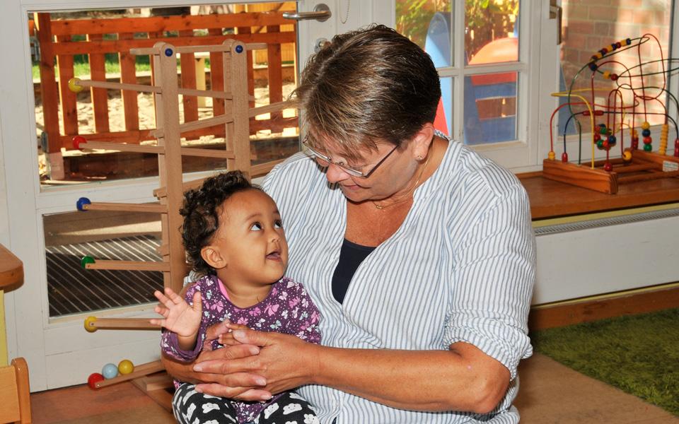 Ein kleines Mädchen sitzt auf dem Schoß einer Erzieherin in der Kita Pusteblume