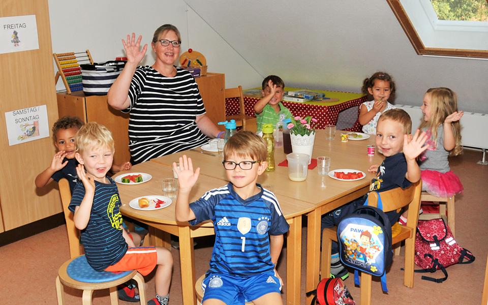Eine Erzieherin frühstückt mit den Kindern in der Kita Pusteblume. Alle winken fröhlich in die Kamera.