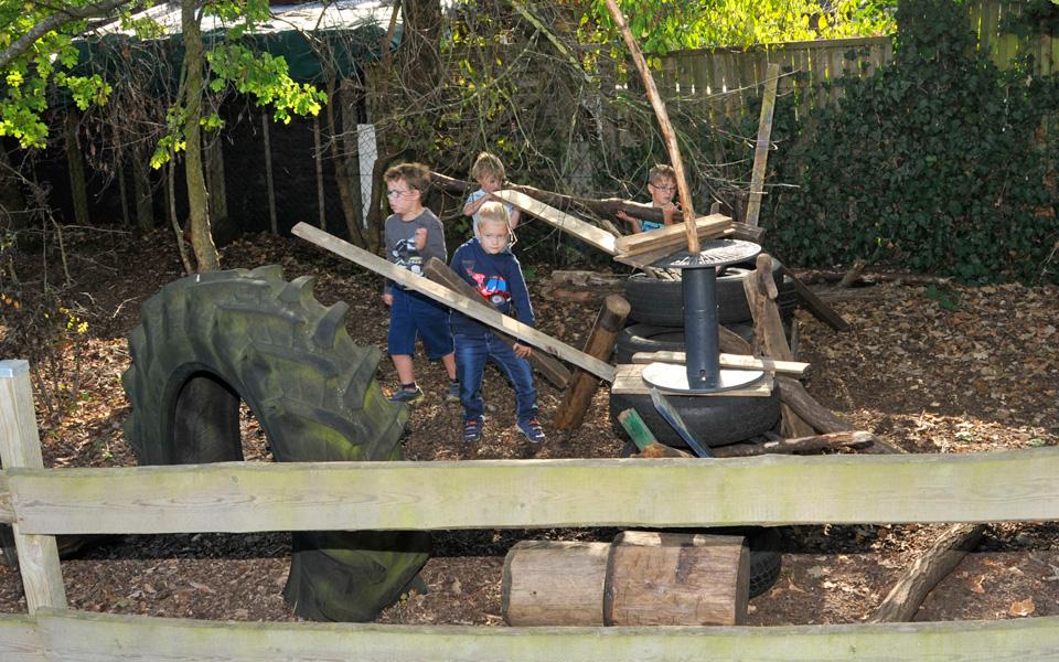 Kinder bauen etwas aus Holz auf dem Außengelände der Kita Pusteblume
