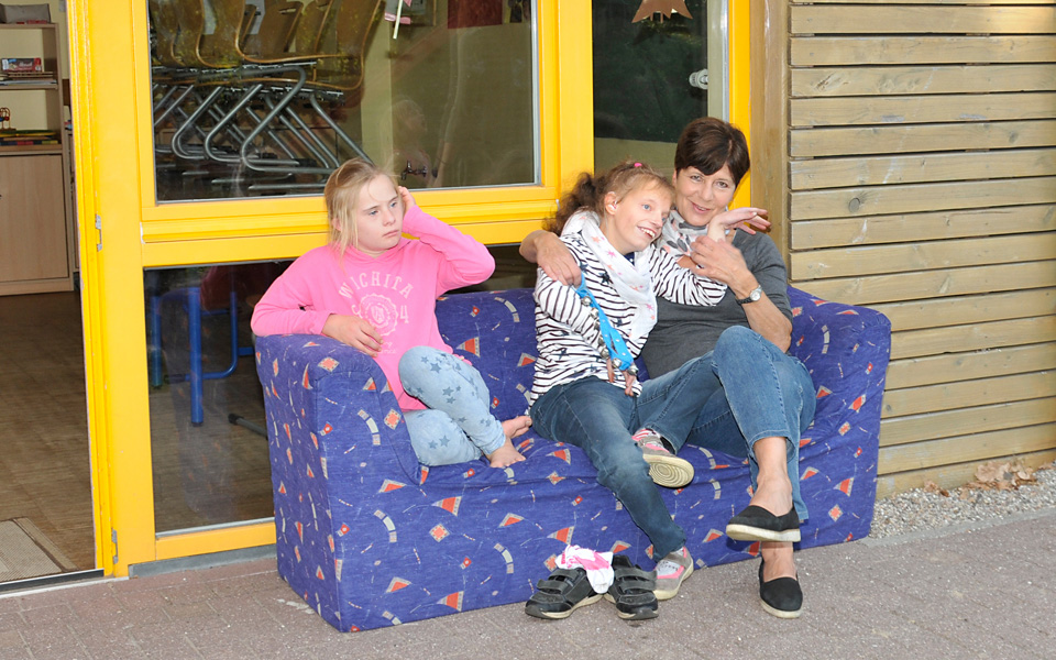 Zwei Mädchen und eine Erzieherin sitzen auf einem Sofa und kuscheln.
