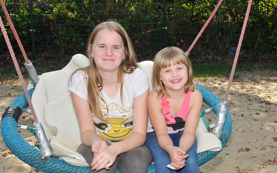 Zwei Mädchen sitzen auf dem Rand einer Nestschaukel und lachen in die Kamera