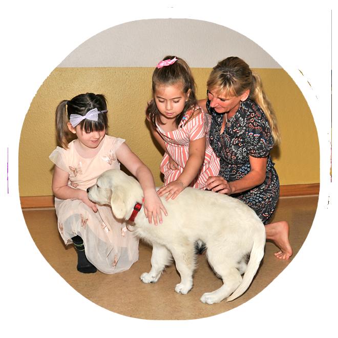 Zwei Mädchen streicheln einen Therapiehund, der an der Hand des einen Mädchens schnuppert. Eine Therapeutin macht den Mädchen Mut dabei.