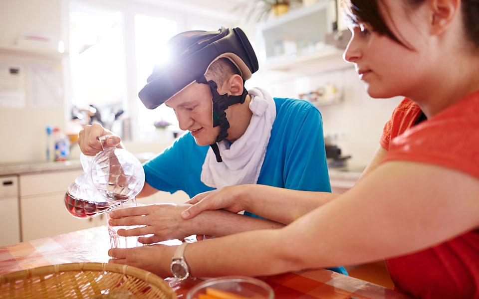 Eine Betreuerin hilft einem behinderten Menschen dabei, Wasser in ein Glas zu gießen.