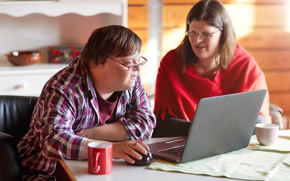 Eine Betreuerin unterstützen einen behinderten Mann beim Umgang mit dem Laptop.