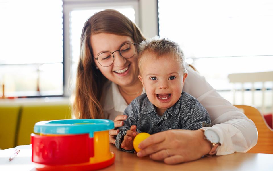 Eine Therapeutin spielt mit einem kleinen Jungen am Tisch mit einem Ball im Rahmen der Frühförderung.