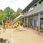 Das Außengelände der Kita Kinderzeit mit großer Sandfläche und Spielgeräten