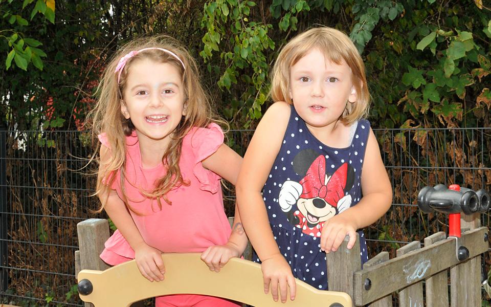Zwei Mädchen spielen auf dem Außengelände der Kita KinderZeit