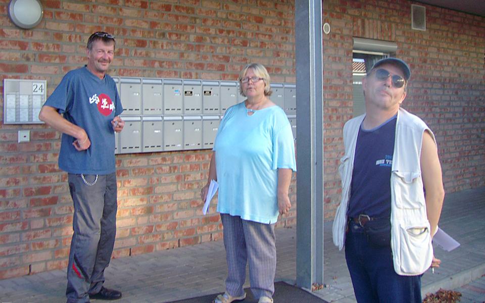 3 Menschen stehen vor einem Haus. Sie gehören zu den ersten Mietern des Wohnprojektes Lindenhain.