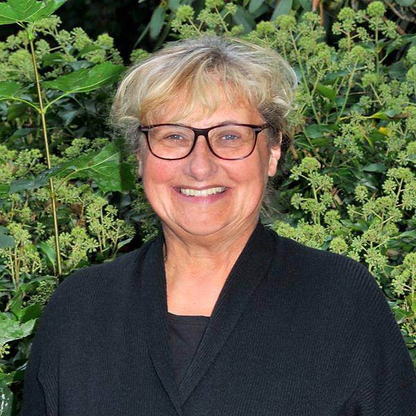 Marina Schulz, Leitung Bereich Wohnen, steht vor grünen Pflanzen und lacht in die Kamera