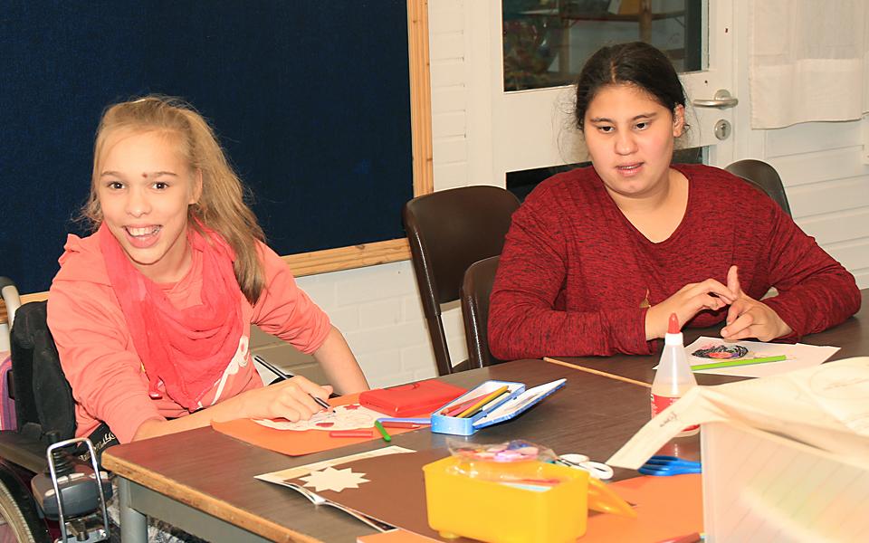 Zwei Mädchen sitzen in der Schule an einem Tisch. Ein Mädchen davon sitzt im Rollstuhl.