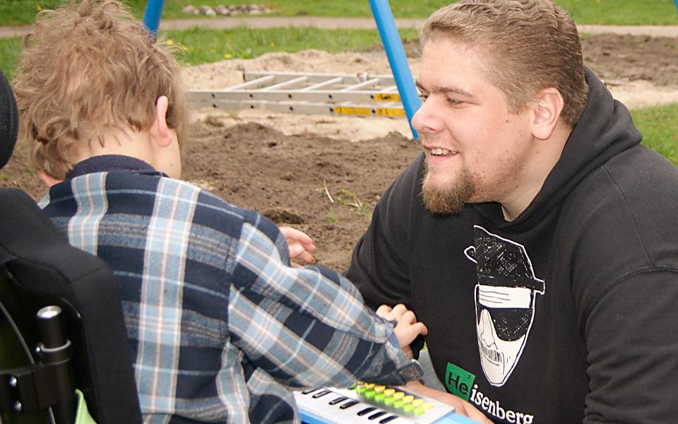 Ein junger Mann unterstützt als Schulbegleitung einen Jungen, der im Rollstuhl sitzt.