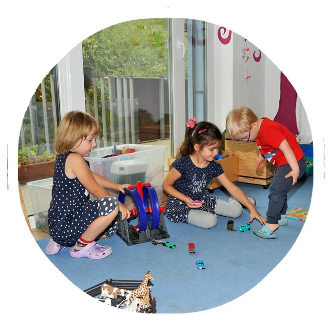 Drei Kinder spielen in einem Gruppenraum der Kita KinderZeit.