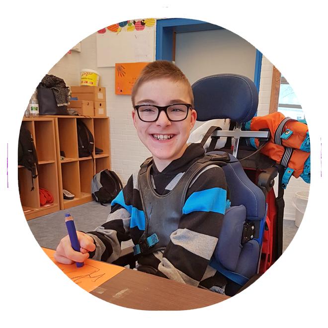 Ein Junge im Rollstuhl sitzt an einem Tisch und zeichnet und lacht fröhlich in die Kamera.